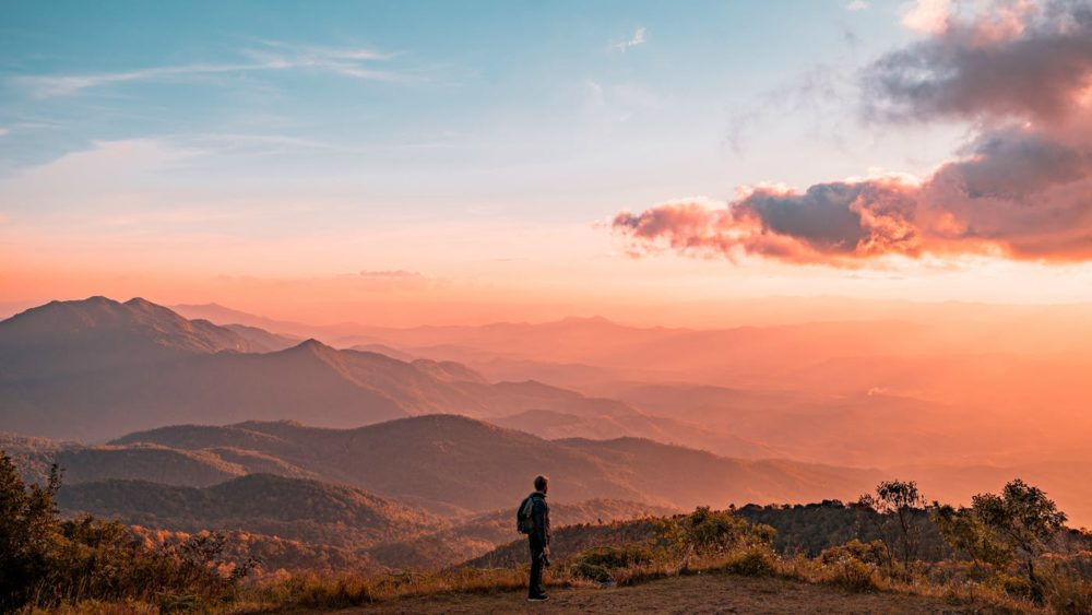 man on mountain at sunset